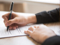 Cropped view of woman holding pen and filling in application form at table